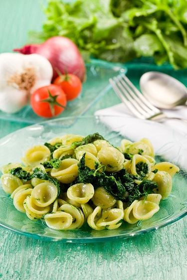 Italian Regional dish with pasta and turnip tops on green glass table